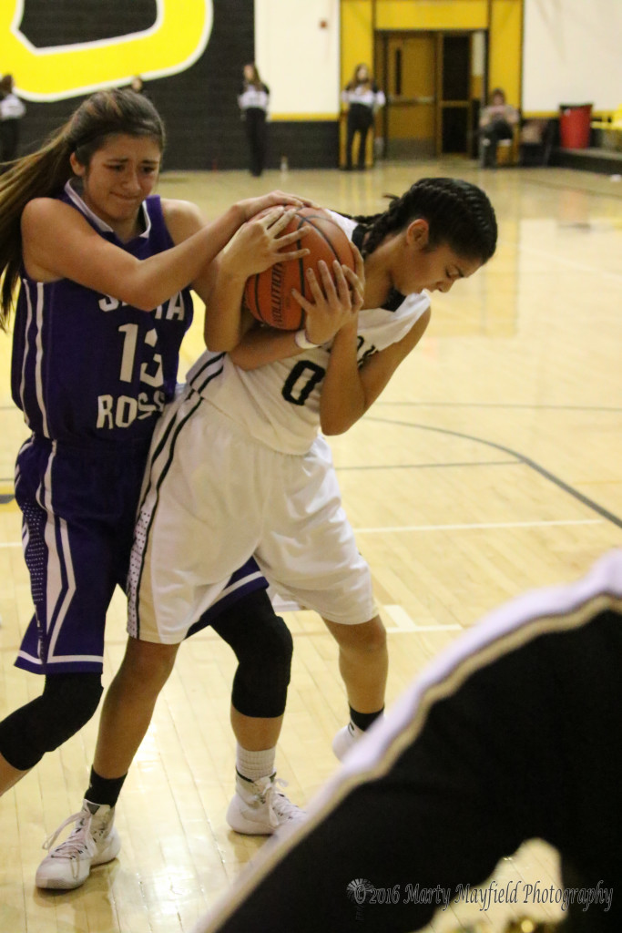 Amber Higgins (13) struggles with Autumn Archuleta (0) for the ball during the varsity girls game Thursday evening
