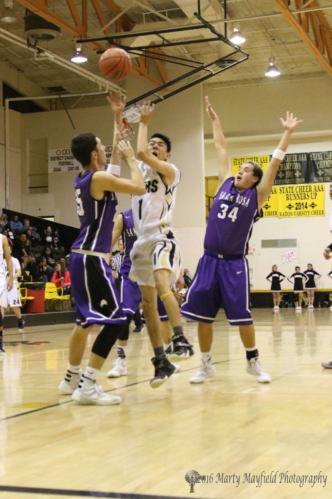Joaquin Romo (25) impedes Jesse Espinoza (1) as he goes in for the shot Javanese Chavez (34) stands by during the boy's varsity game in Tiger Gym