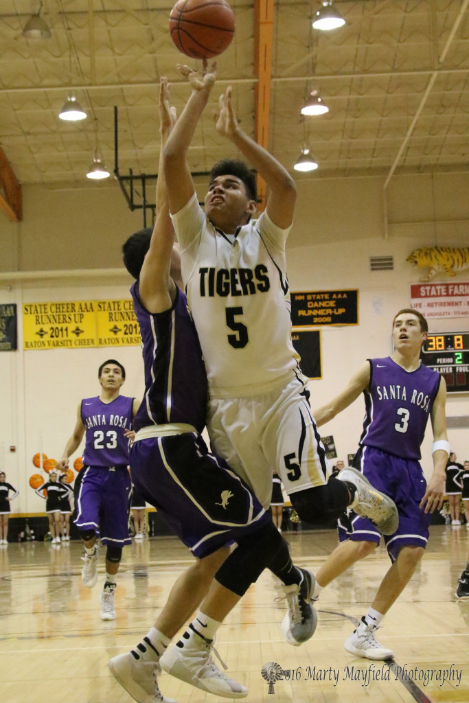 Austin Jones (5) drives the lane as Joaquin Romo goes for the block and draws the foul in the boy's varsity game Thursday evening in Tiger Gym