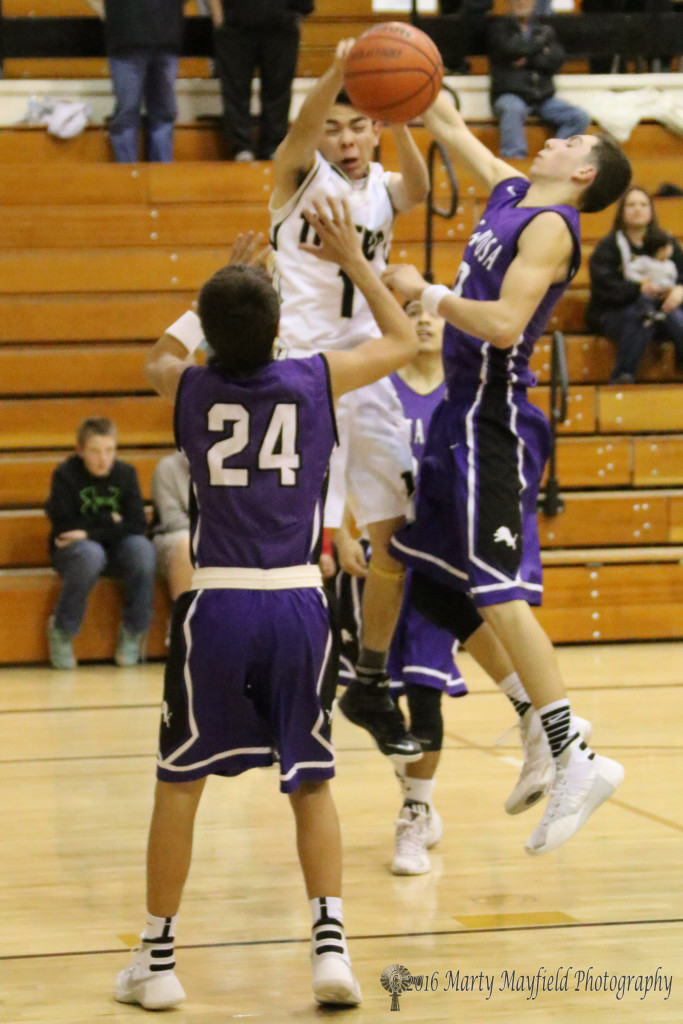 Jesse Espinoza goes in for the shot while Joseph Esquivel (24) and Mark Saiz go for the blocks Thursday evening