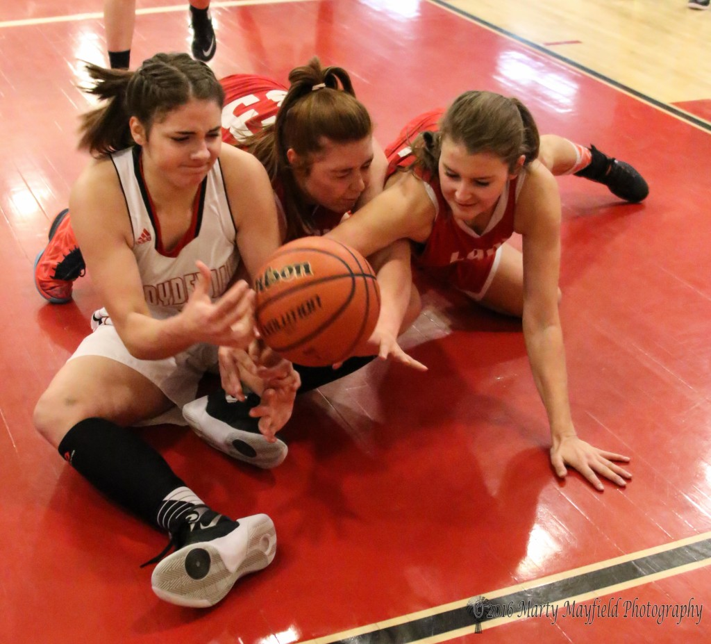 Katy Scott wrangles with Mariah Vanderlei and Gentry Haukabo during the District Championship game in Springer