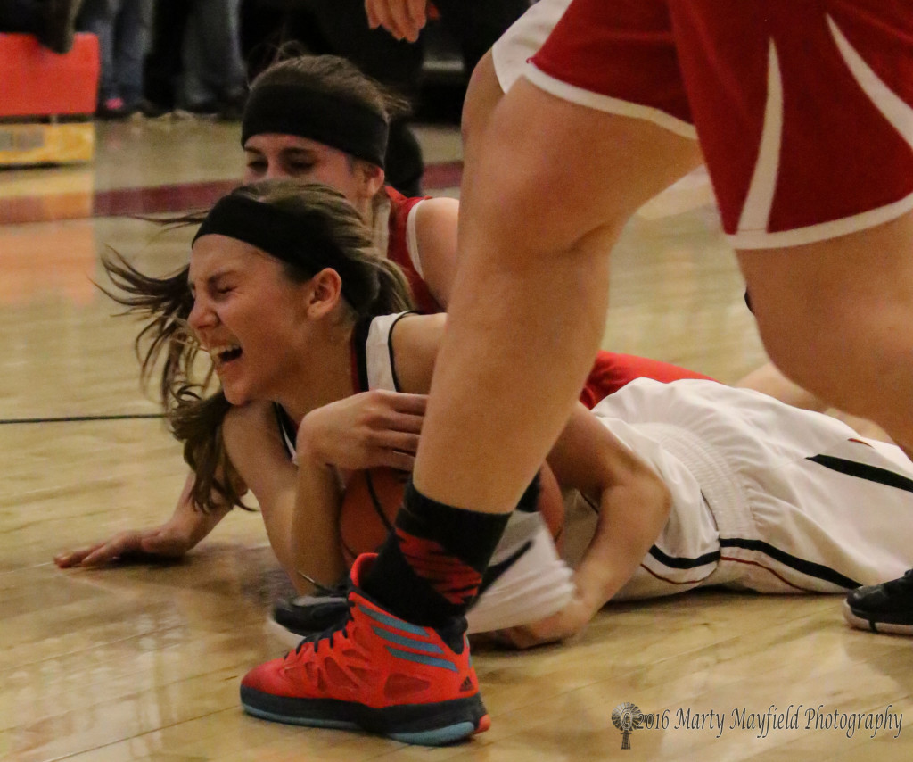 Hannah Burton goes to the floor after the ball with Shaylee Reinde right behind her in this physical district championship game Saturday evening.