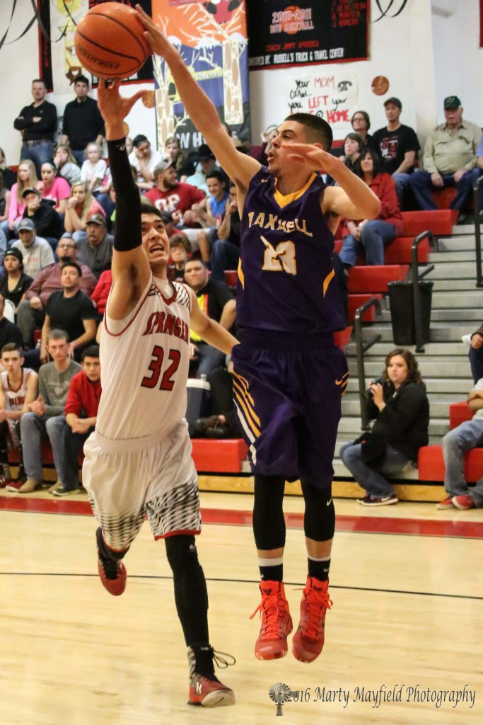 Thomas Mitchell (23) and Zac Caldwell (32) reach out for the ball on the rebound.