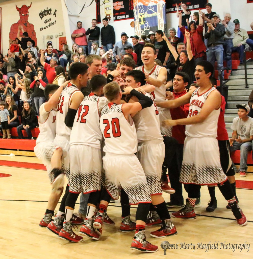 The celebration begins as the boys crowd around Jacob Pacheco after he made the winning shot for Springer