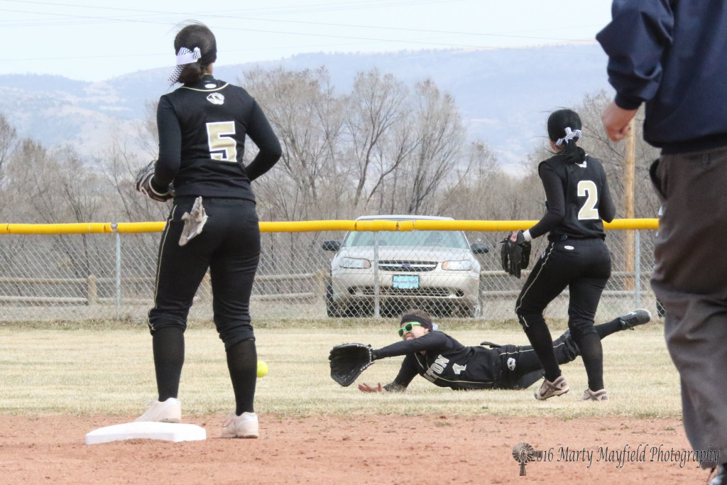 Montana Trujillo makes a dive for the ball but strong winds made fielding fly balls difficult Tuesday afternoon.