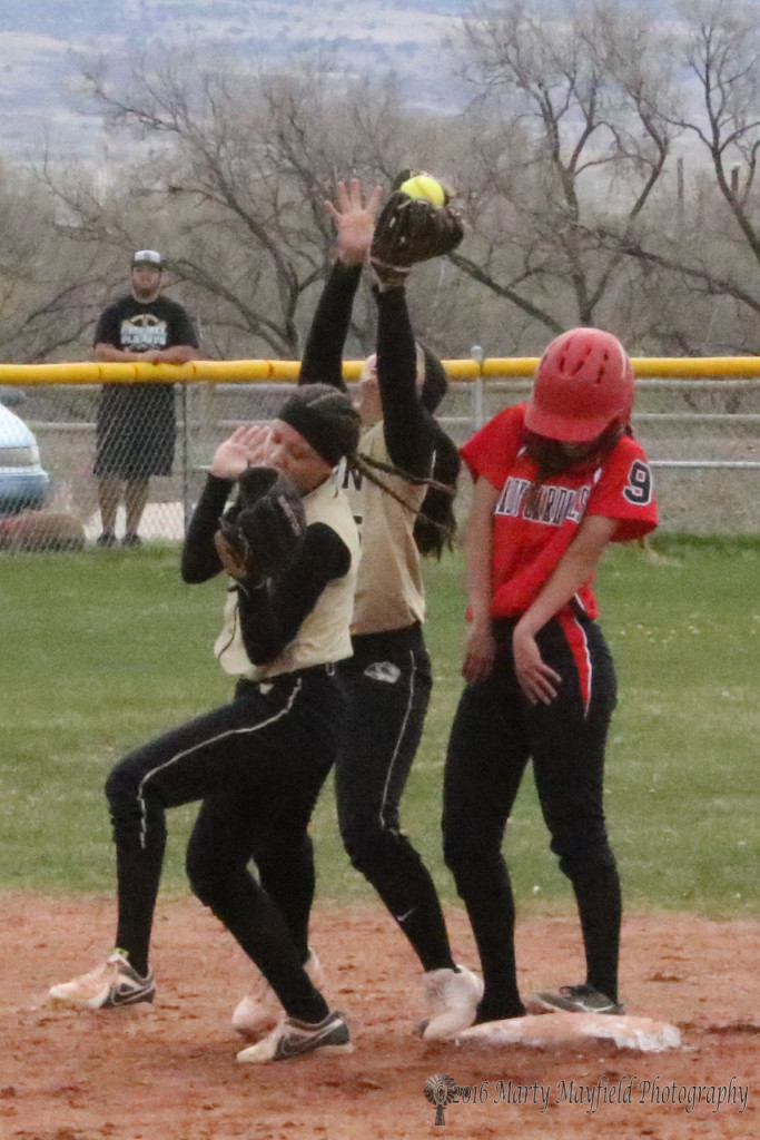 Sophia Madellini reaches for the fly ball as Estrell Vargas and Lady Cardinal Mikayla Roybal try not to get hit