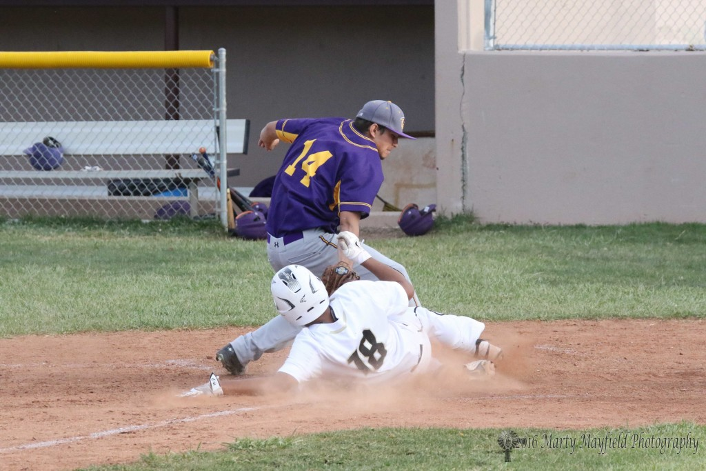 Austin Jones slides for home as pitcher Zach Martinez reaches in for the tag. Jones was called out on the play.