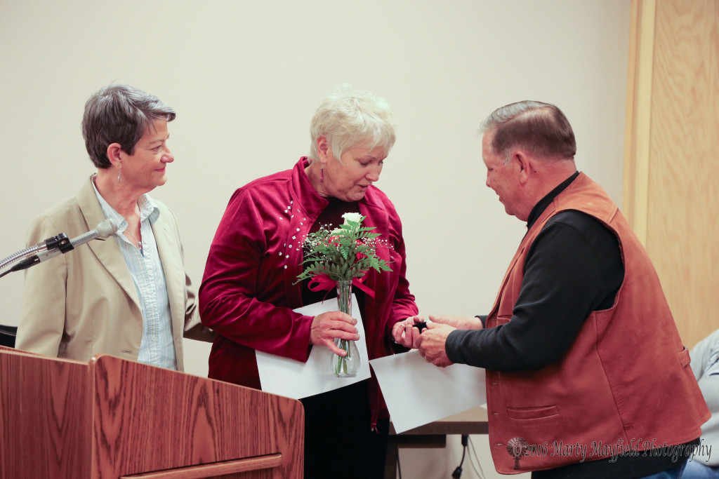 Nancy Poe accepted the You Rock Award from Commissioner Ron Chavez and Adrianne Coleman for her volunteerism during the recent winter storm event in March.