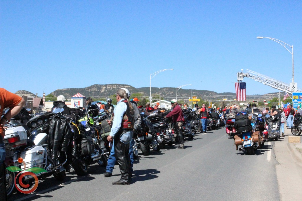 Bikes line Clayton Road near the visitor's center as an American Flag hangs over the street. The flag is provided by Raton Fire and Emergency Services
