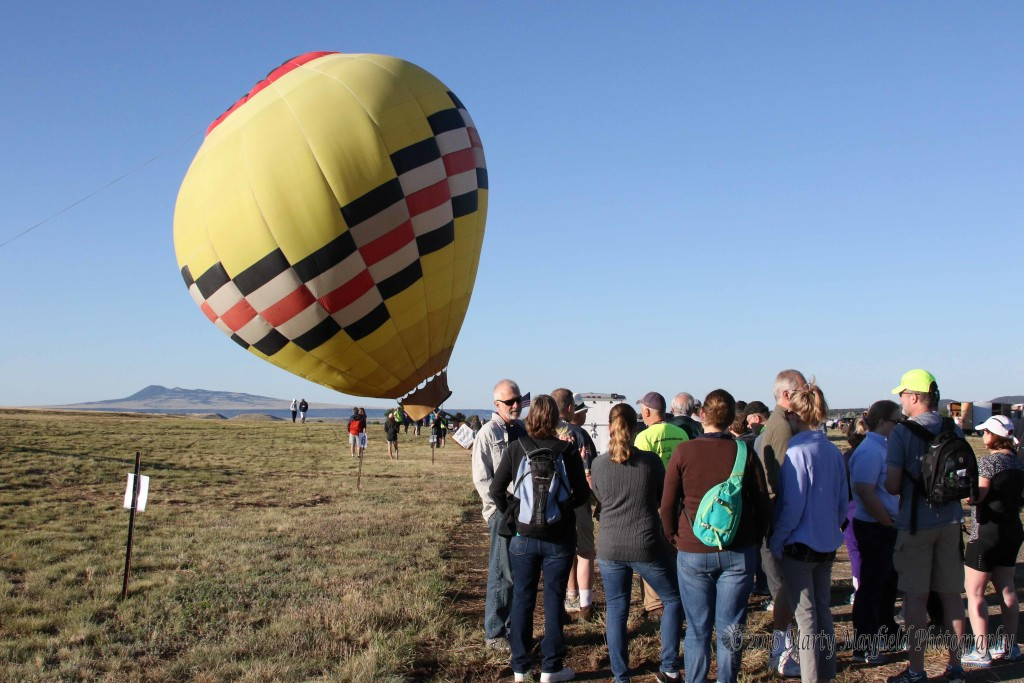 Pilot Bill Dimmitt heats up the balloon Sunrise Angel as spectators congregation the La Mesa Airfield. Winds once again delayed lift off of many of the balloons.