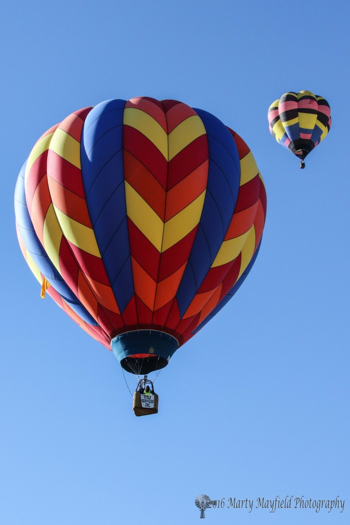 Up and away as Saki Bomber and Highlighter float south. Winds changed directions several times during the morning with many balloons delaying light off waiting for more favorable winds.