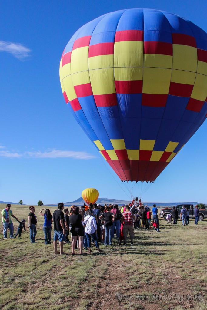 The kiddos are lined up waiting for Vacation, piloted by Janet Rusler to start giving tethered rides to the kiddos Sunday morning at the 2016 International Santa Fe Trail Balloon Rally