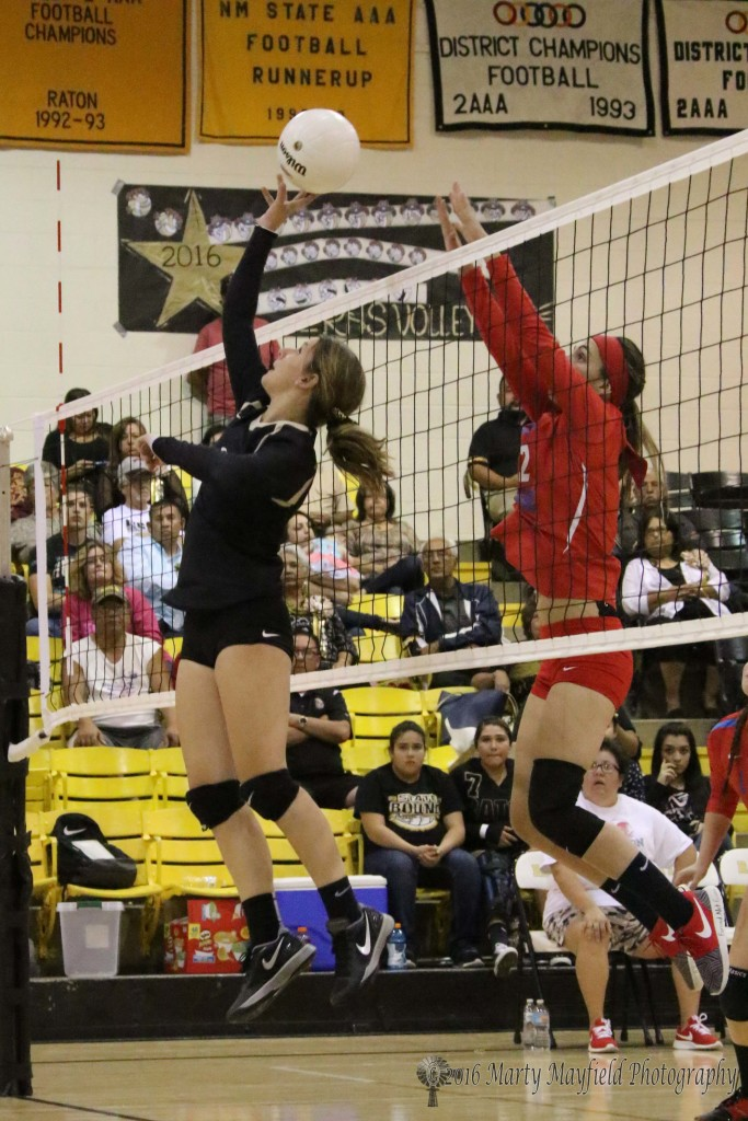 Camryn Mileta makes the tip over the net as Tiana Garcia goes up for the block