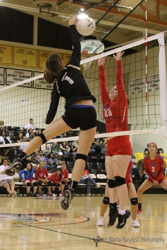 Camryn Mileta makes the hit over the net while Samantha Ogata goes for the block