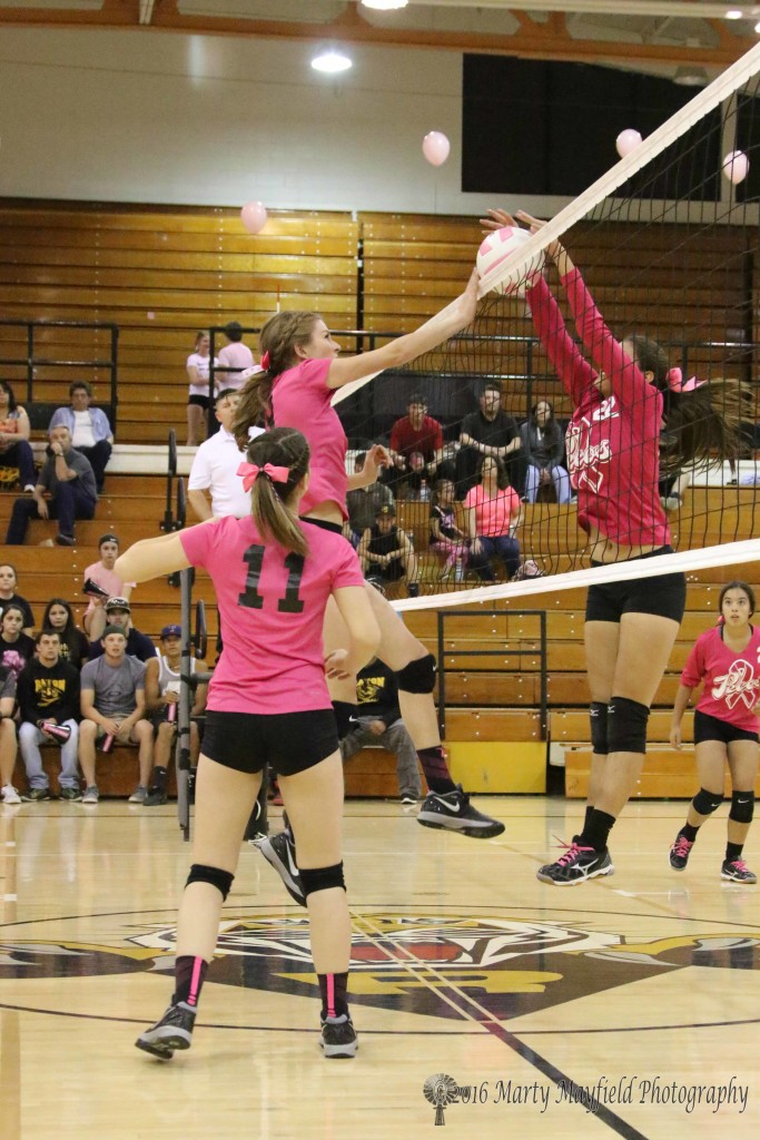 Alina Pilmore meets Faith Flores at the net as Pilmore slams the ball over the net as Flores goes for the block.