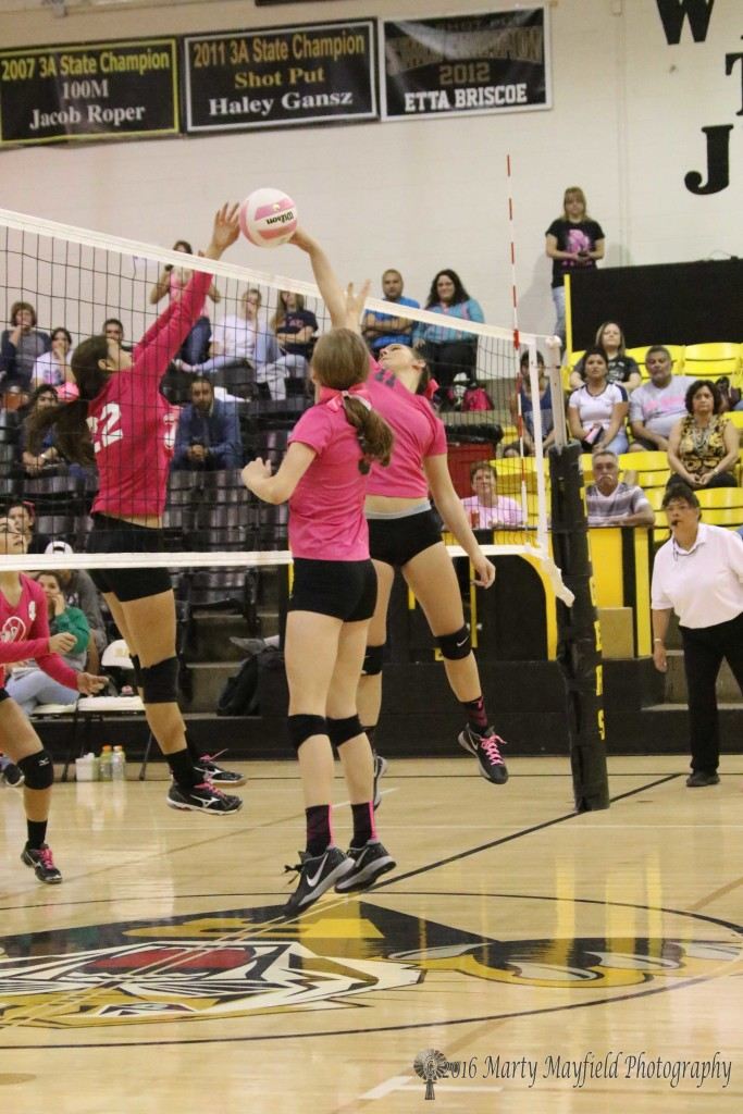 Faith Flores goes for the block as Camryn Mileta makes the tip over the net.