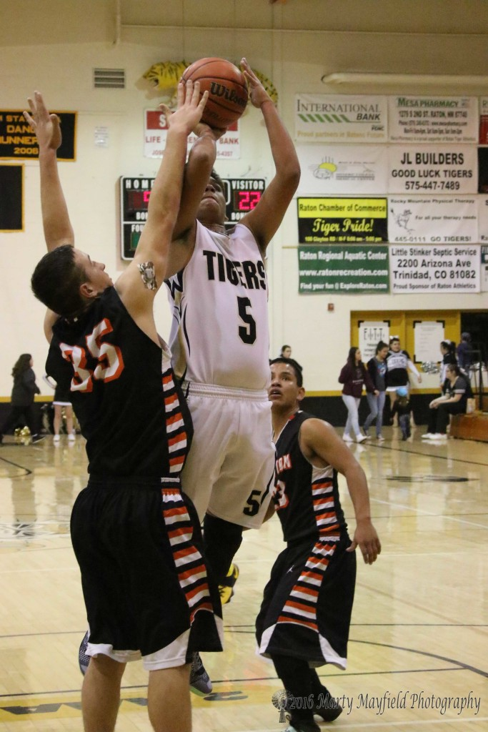Raton's Austin Jones puts the ball up as Kobe Montoya goes for the block.