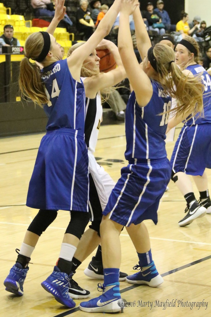 Riley Clavel (14) and Kindel Smith (10) wrap up McKenna Hittson during the consolation championship game during the 2016 Cowbell