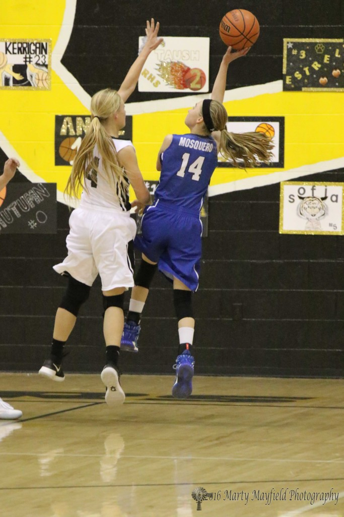McKenna Hittson (4) goes for the block as Riley Clavel (14) takes the shot late in the game.