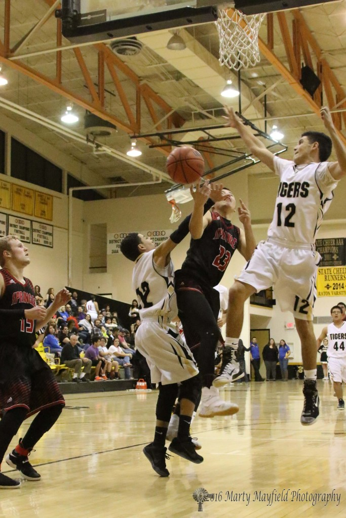 Estevan Romero (23) drives through Richie Acevedo (22) and Ismael Tafoya (12) on his way to the basket during the 2016 Cowbell 3rd place game.