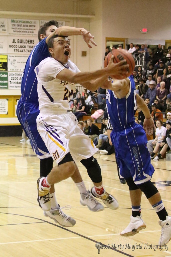 Jeremy Cintas gets an arm in the way while TJ Madrid joins in the block as Andrew Archuleta drives the lane during the boys championship game of the 2016 Cowbell in Raton