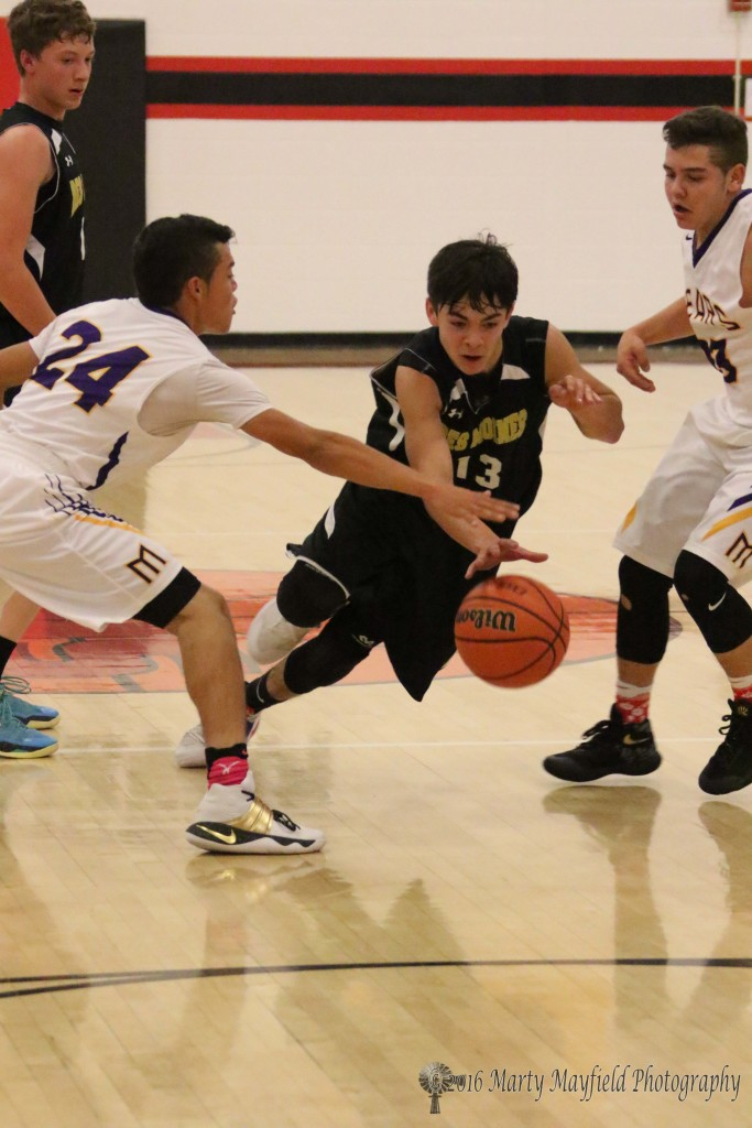 Demon Isaiah Trujillo threads it through Jeremy Archuleta as Andrew Archuleta reaches for the ball during game four of the 2016 Cowbell in Springer
