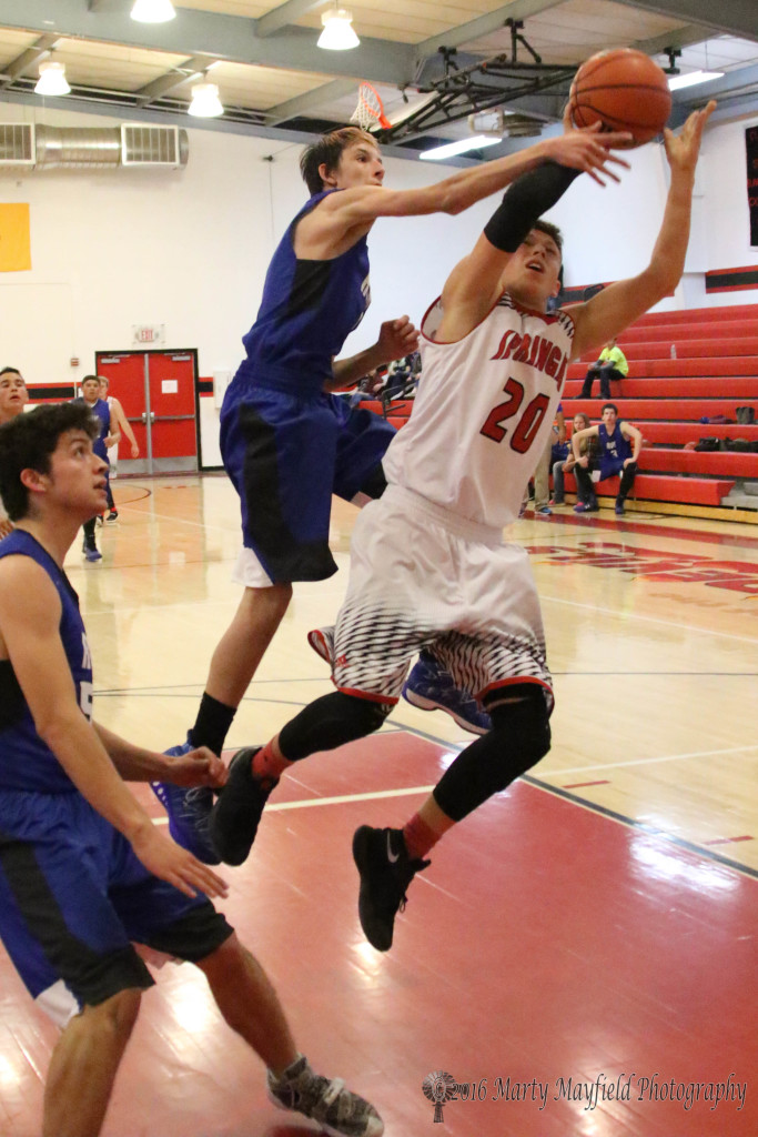 Gabe Garcia (20) goes for the lay-up as Ryan Johnson gets a hand on the ball for the block during game 8 of the 2016 Cowbell in Springer Wednesday night.
