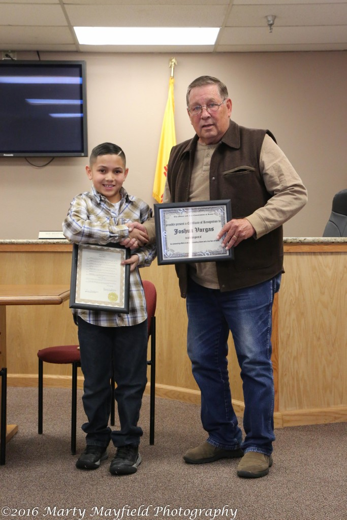 Commissioner Ron Chavez presents Joshua Vargas with a proclamation and a certificate of recognition for his life saving efforts.