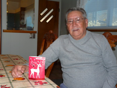 "Former Dawson Coal Camp resident Edward Zavala with a Christmas card he received from another former Dawsonite, Marcel Rivera, who wrote in the card: ""I'm thinking of Dawson at Christmas. We had nothing. We had no toys, not too much to eat, but we were all happy. And now we have everything, including everything we want to eat, but we're not as happy as we used to be."""