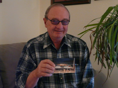 "George ""Judo"" Yaksich with a photo depicting the Christmas lamb roasting on a spit, a tradition that was carried on in his family from the early days in Koehler to recent times. Yaksich lived in the Koehler Coal Camp when he was a youngster."