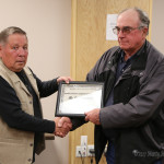 Carl Swanson receives a certificate of appreciation for the painting he has done that hangs in the city commission chambers.