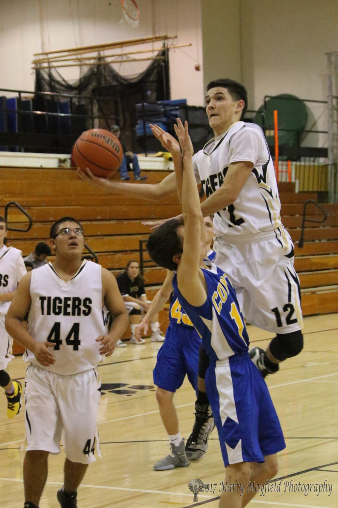 Ismael Tafoya drives the ball to the basket as Caleb Jaramillo takes the foul during the JV game Thursday evening in Tiger Gym