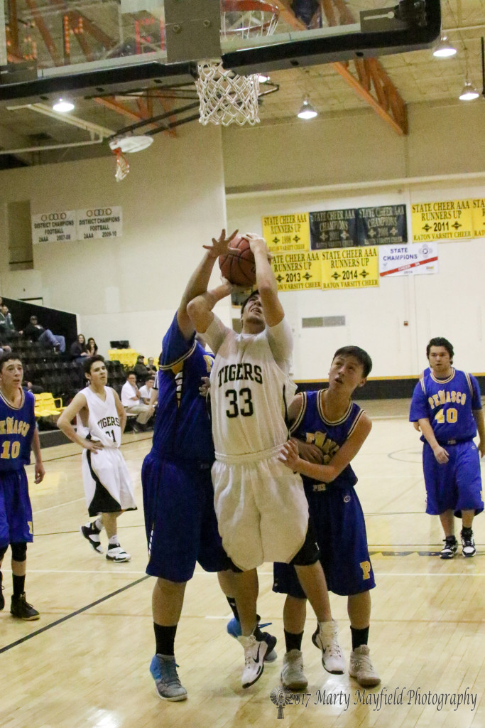 Christian Snyder takes the shot as Danny Esquivel goes for the block while Jude Encinias looks on from behind.