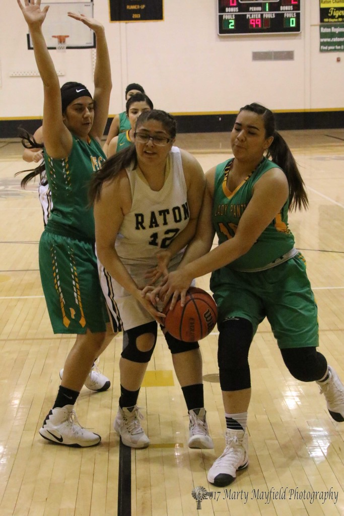Mariah Saenz (12) drives down the lane only to be met by Sativa Herrera and Mikayla Gonzales. Herrera stole the ball as Pecos did many times in the game Saturday afternoon in Tiger Gym