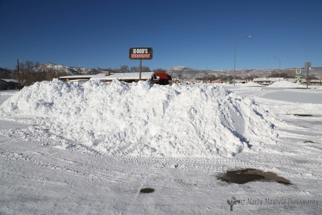 Snow is piled high in the K-Bobs parking lot Friday afternoon