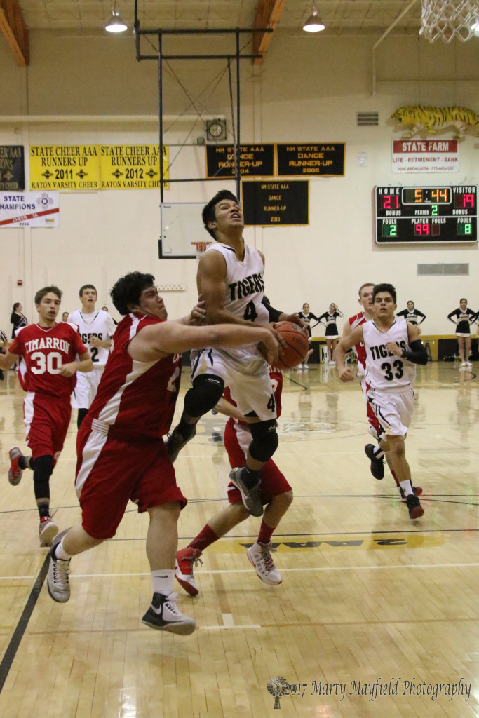 Joe Serna (21) interferes just enough to prevent Jonathan Cabriales from making the shot in the second quarter of the game Thursday in Tiger Gym