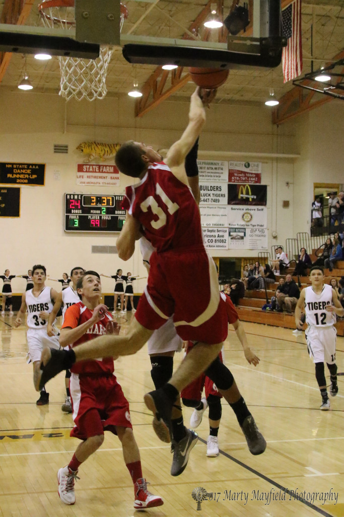 Austin Luksich (31) gets a hand on the ball as Jonathan Cabriales goes for the lay-up.