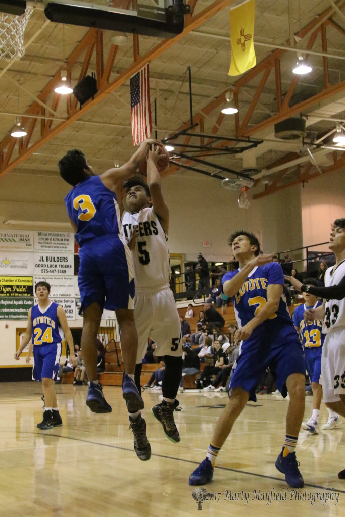 Vishal Patel (3) despite the height difference gets a hand on the ball as Austin Jones goes up for the shot during the varsity game Thursday evening in Tiger Gym