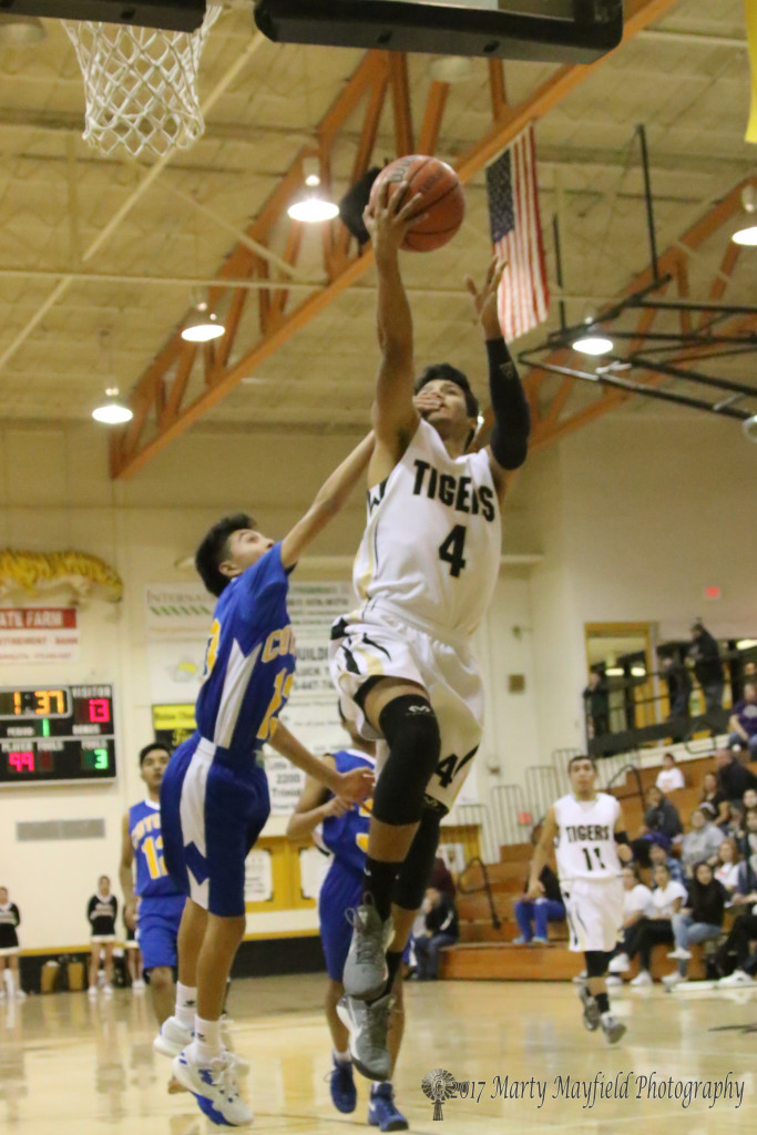 Jonathan Cabriales (4) drives to the basket as Abenicio Maestas (13) goes for the block during the varsity game Thursday evening.
