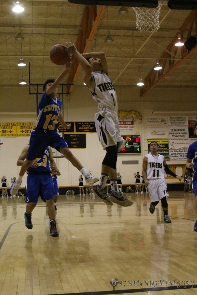 Jesse Espinoza (1) goes in for the lay-up as Abenicio Maestas (13) gets a hand on the ball in the second quarter Thursday evening