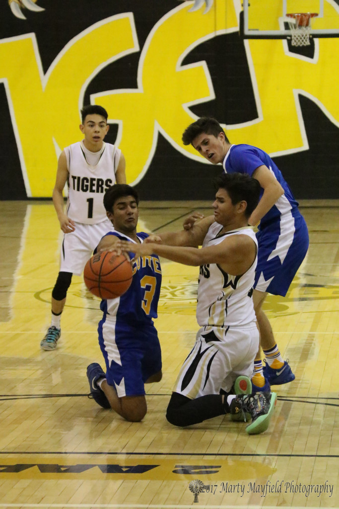 On the floor the boys wrangle for the ball as Vishal Patel (3) and Austin Jones work for control of the ball Thursday evening during the varsity game.