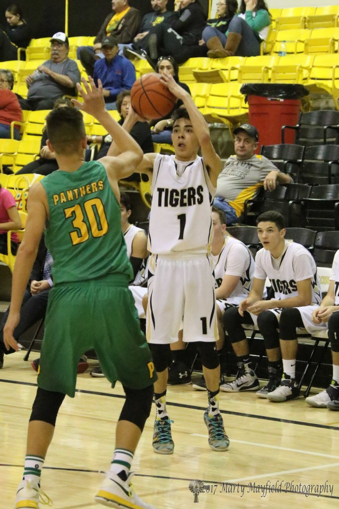 Jesse Espinoza takes a 3-point shot, Espinoza put in three 3-pointers for the Tigers Saturday evening.