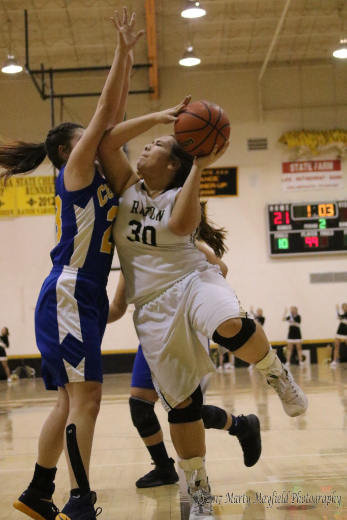 Sydni Silva (30) drives for the basket on her way to two of her 12 points on the evening as Teddee Saavedra works for the block