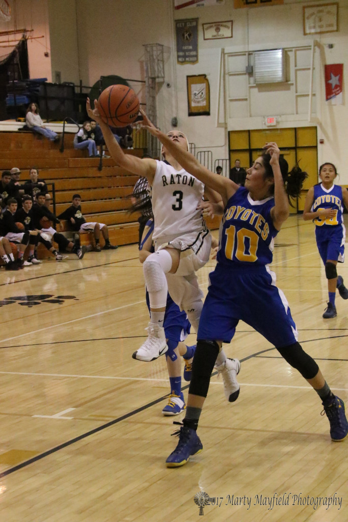 Estrella Vargas (3) drives in for the lay-up as Jaelyn Garcia (10) gets a finger on the ball to disrupt the shot.