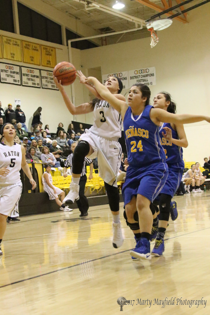Estrella Vargas(3) drives the lane as Megan Romero(24) gets a hand in the way during the varsity game Saturday evening