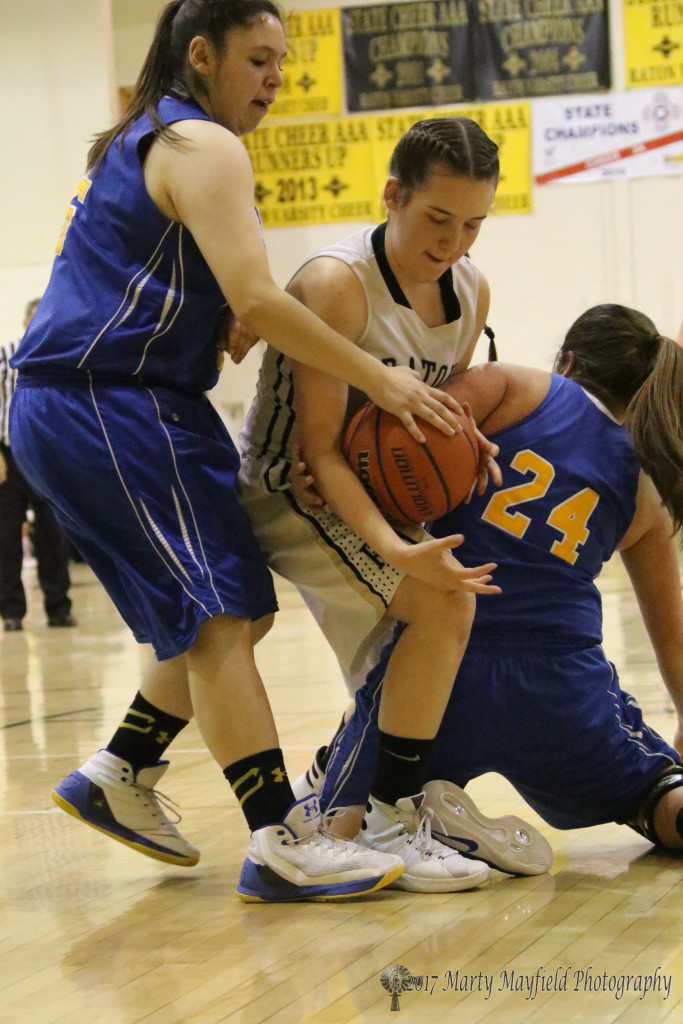 Halle Medina tangles with Megan Romero (24) and Jordyn Vargas (55) for the ball in the varsity game Saturday evening