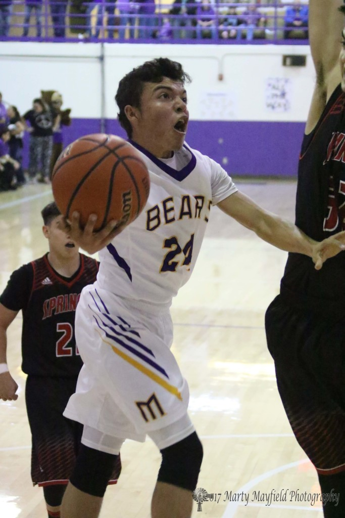 The intensity of they championship game shows on the face of Andrew Archuleta as he drives the lane into Zach Sanchez Saturday evening in Maxwell.