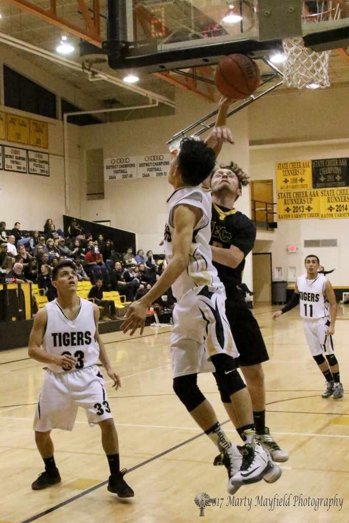 Jesse Espinoza takes the baseline and attempts a backwards lay-up but is fouled by Justin Vigil early in the district tourney game Wednesday evening in Tiger Gym