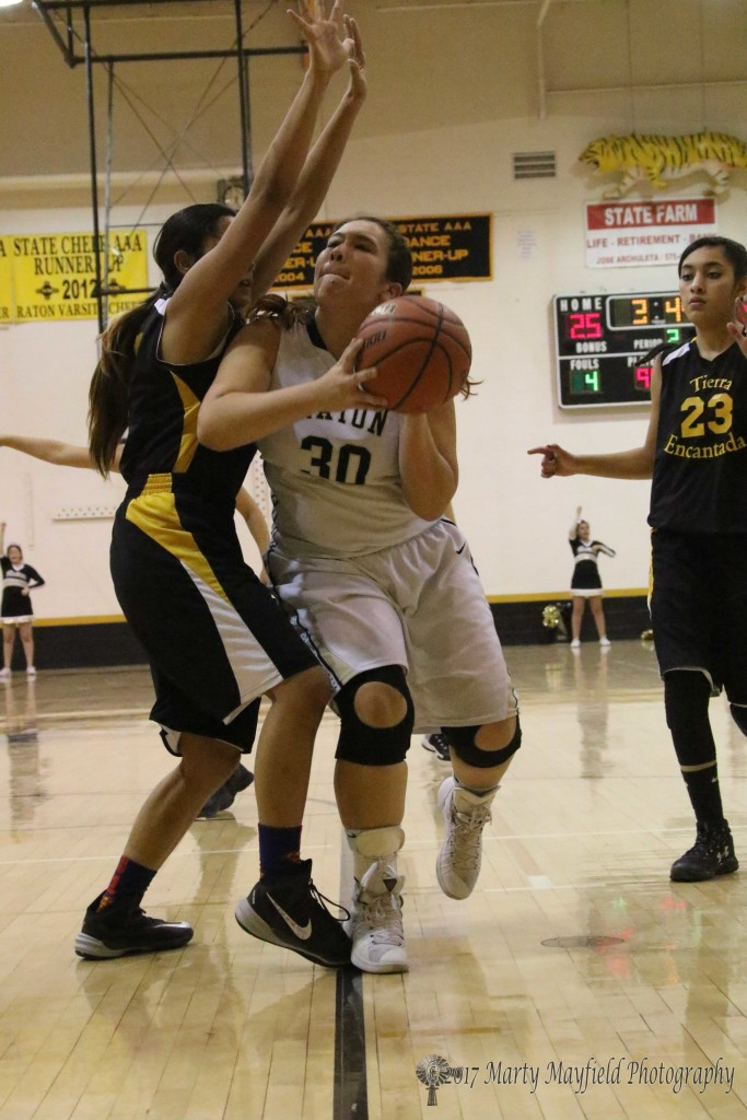 Sydni Silva drives the lane Thursday evening against Ida Contreras during the district tourney game in Tiger Gym