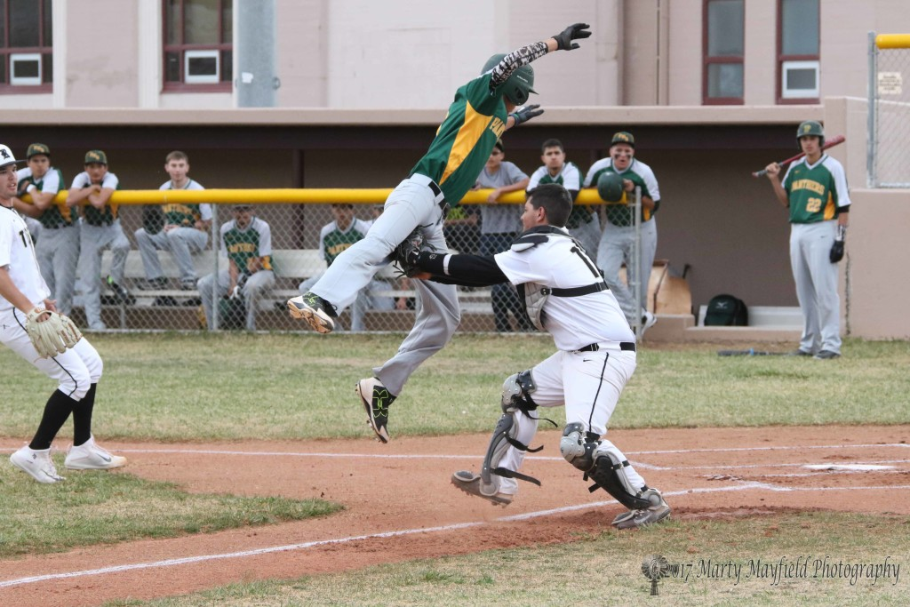 William Holland makes the tag as Mario Archuleta attempts to steal home during the first district game in Raton.